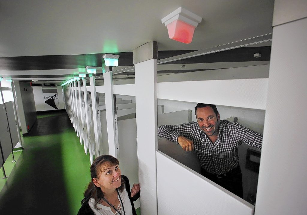 Chrissy Whitman, left, operations manager for the Hollywood Bowl, and Allen Klevens, co-founder of Tooshlights, show a lighting system designed by Klevens that lets female Bowl patrons know when restroom stalls are occupied or vacant. (Mel Melcon / Los Angeles Times)